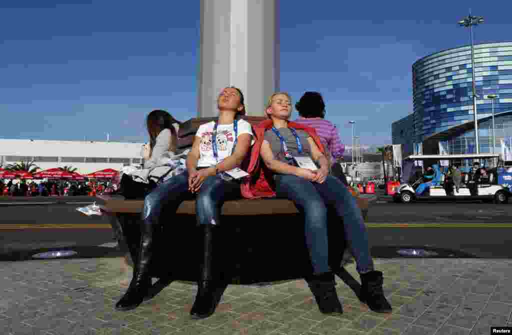 Women sun themselves in 60-degree weather at the Olympic Park, Sochi, Russia, Feb. 12, 2014.