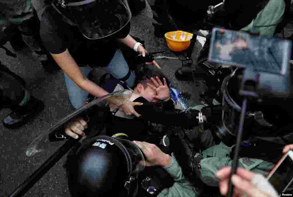 Agentes de la policía antidisturbios detienen a un manifestante contra la ley de extradición durante una marcha en el barrio de Sham Shui Po en Hong Kong, China, 11 de agosto de 2019. Un video del incidente fue publicado por el sitio web Hong Kong Free Press.