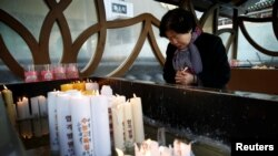 A woman prays for her grandchild taking the annual college entrance examinations at a Buddhist temple in Seoul, South Korea, Nov. 17, 2016.