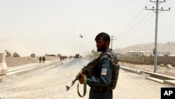 FILE - An Afghan policeman stands guard near the site of a suicide bomb attack on a NATO convoy in Kandahar, south of Kabul, Afghanistan, Aug. 2, 2017.
