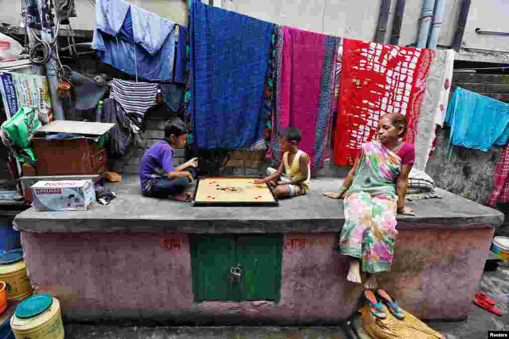Boys play carrom at a slum area in Kolkata, India.