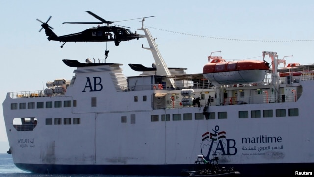 Members of the special forces abseil from a UH-60A Black Hawk helicopter as others use a rope ladder to board a ship during a boarding drill, part of the Eager Lion military exercise, in the coastal city of Aqaba, June 19, 2013.