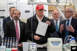 FILE: President Donald Trump holds up a picture as he listens during a meeting with Health and Human Services Secretary Alex Azar, left, Associate Director for Laboratory Science and Safety Steve Monroe, and Centers for Disease Control and Prevention.