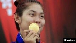 កញ្ញា ស៊ន សៀវម៉ី អាយុ១៩ឆ្នាំ បង្ហាញមេដាយមាសរបស់កញ្ញាទៅកាន់អ្នកកាសែតនៅក្រោយសន្និសីទព័ត៌មានមួយក្នុងក្រុងភ្នំពេញ កាលពីថ្ងៃទី៦ ខែតុលា ឆ្នាំ២០១៤។ កញ្ញា សៀវម៉ី ជាកីឡាការិនីដែលបានឈ្នះមេដាយមាសដំបូងបំផុតរបស់កម្ពុជានៅក្នុងការប្រកួតកីឡាអាស៊ី Asian Games ដោយបានឈ្នះនៅក្នុងវិញ្ញាសាកីឡាតេក្វាន់ដូក្នុងការប្រកួតកីឡា Asian Games ទី១៧នៅទីក្រុងអ៊ីនឈិនប្រទេសកូរ៉េខាងត្បូង។ (REUTERS)