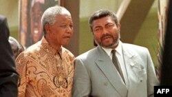 Le président sud-africain Nelson Mandela (à g.) avec son homologue ghanéen Jerry Rawlings lors de l'ouverture du sommet de l'Organisation de l'unité africaine à Ouagadougou, Burkina Faso, le 8 juin 1998.