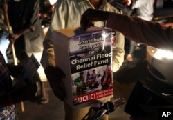 Members of Socialist Unity Center of India collect relief funds for Chennai flood victims at a traffic crossing in Hyderabad, India, Dec. 8, 2015.