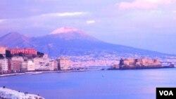 La imagen es una postal de Nápoles con el legendario Volcán Vesubio en el horizonte.