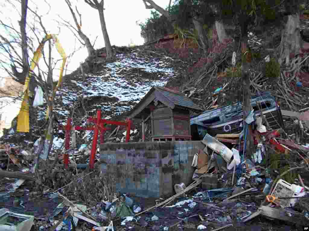 A wrecked car rests above a Shinto shrine in Kamaishi, Japan, March 17, 2011 (H. Ridgwell)