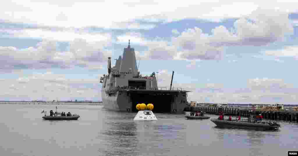 With the U.S. Navy's well deck ship USS Arlington stationed against its pier at Naval Station Norfolk in Virginia, divers in small boats approach a test version of NASA's Orion crew module during the stationary recovery test. The test is helping to ensure that when Orion returns from deep space missions and splashes down in the Pacific Ocean.