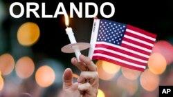 Yon moun ki pataje dèy fanmi viktim yo, tap patisipe nan yon retrètoflanbo nan vil Atlanta, Eta Jòji, kote li kenbe yon chandèl ak yon ti drapo Ameriken aprè atak ki te fèt nan bwatdenui Orlando a dimanch 12 jen 2016 la (Foto: AP Photo/David Goldman).