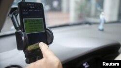 Một tài xế GrabTaxi dùng điện thoại để kiểm tra hóa đơn cho một khách hàng ở Hà Nội, Việt Nam, ngày 9/9/2015.