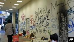 1月24号,希腊一名妇女从雅典一个地铁站外的流浪者身边走过。