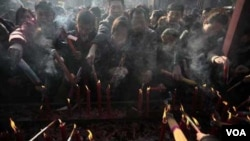 Warga Tiongkok menyalakan lilin tahun baru Imlek.