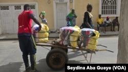 Un marchad achemine des packs de fripes sur un chariot des magasins vers le marché pour la vente au détail à Colobane, 17 juin 2017. (VOA/ Seydina Aba Gueye)