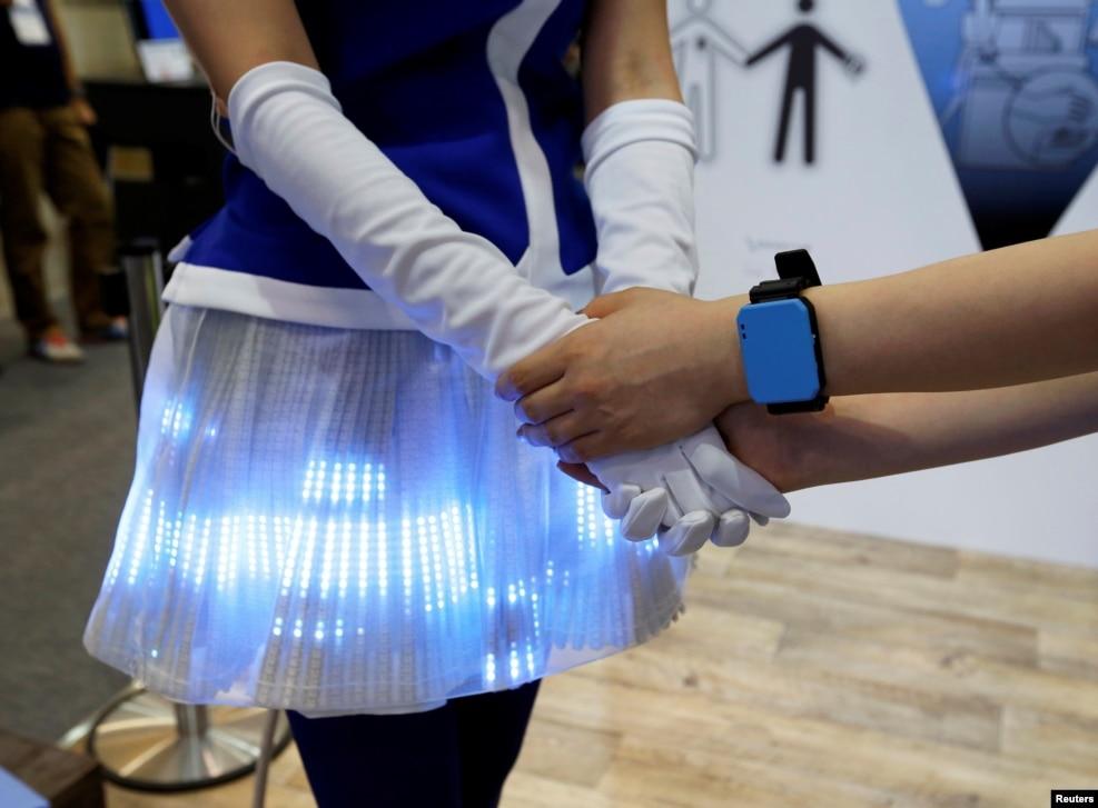 Qadınlar Panasonic şirkətinin İnsan Bədəni Kommunikasiya Cihazını nümayiş etdirir. Çiba, Yaponiya.
