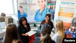 FILE - Job seekers listen to a recruiter at the Colorado Hospital Association job fair in Denver, Colorado, Oct. 4, 2017.