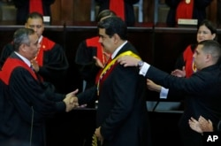 FILE - Venezuela's President Nicolas Maduro, center, shakes hands with Supreme Court President Maikel Moreno as his presidential sash is adjusted, after he took the oath of office in Caracas, Jan. 10, 2019. Maduro's second, six-year term starts amid internationa