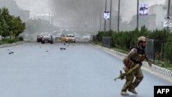 Pasukan keamanan Afghanistan berlari menuju lokasi serangan bunuh diri di depan gedung parlemen Afghanistan di Kabul, Senin (22/6). Afghanistan menuduh agen intelijen Pakistan (ISI) membantu serangan Taliban ini.