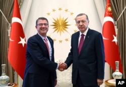FILE - Turkey's President Recep Tayyip Erdogan, right, and U.S Secretary of Defense Ash Carter shake hands before a meeting in Ankara, Turkey, Oct. 21, 2016.
