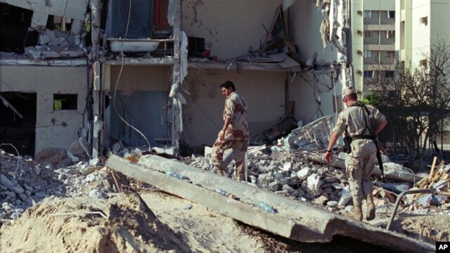 Binh sĩ Mỹ và Ả Rập Xê Út đi trên đống đổ nát của khu chung cư 8 tầng Tháp Khobar gần thành phố Dharan bị đánh bom vào ngày 25 tháng 6 năm 1996 làm 16 binh sĩ không quân Mỹ thiệt mạng và hàng trăm người khác bị thương.