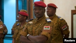 FILE - Burkina Faso Prime Minister Yacouba Isaac Zida listens as an official reads the names of transitional government ministers, in Ouagadougou, Burkina Faso.