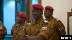 Burkina Faso Prime Minister Isaac Zida listens as an official reads the names of transitional government ministers in Ouagadougou Nov. 23, 2014.