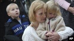 Bà Barbara Wells bế con gái Olivia 3 tuổi dự buổi tưởng niệm nạn nhân vụ cuồng sát tại Trường Tiểu học Sandy Hook ở Newtown, Connecticut, 12/17/12