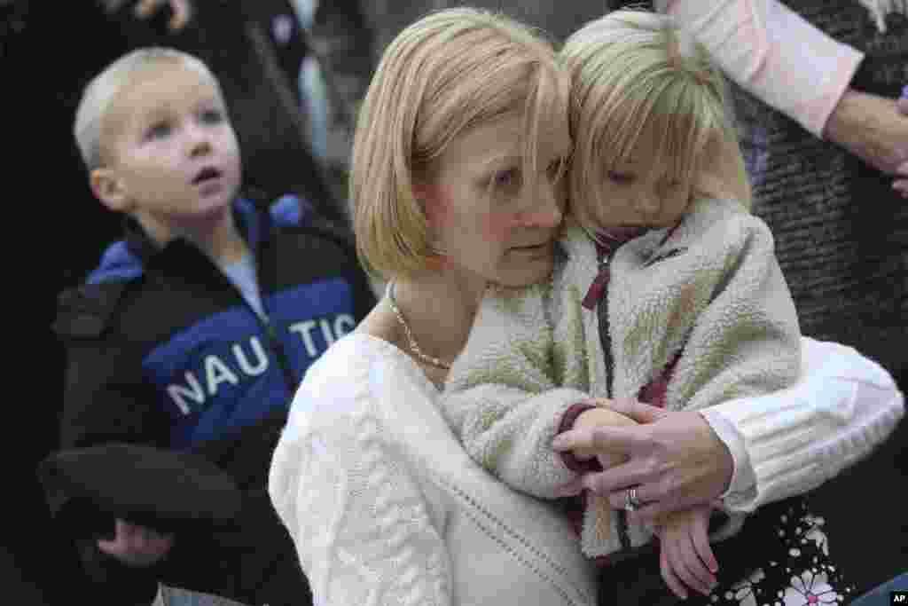 2012年12月17日,康州谢尔顿的Barbara Wells抱着三岁的女儿Olivia在一处临时纪念地凭吊桑迪.胡克小学枪杀惨案的遇难者。