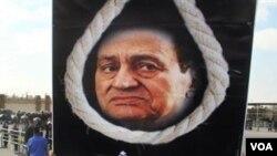Seorang warga Mesir mengusung poster Mubarak dengan tali gantungan disertai tulisan 'Pengadilan Rakyat', di depan pengadilan di Kairo (28/12).