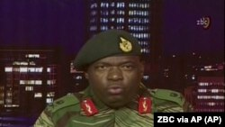 In this image made from video, Major Gen.Sibusiso B. Moyo, spokesperson for the Zimbabwe Defense Forces addresses to the nation in Harare, Zimbabwe Wednesday, Nov. 15, 2017.