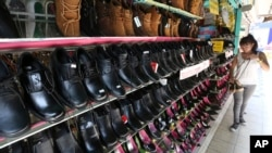 FILE - A woman is seen browsing for shoes at a store in downtown Chiang Mai, northern Thailand.
