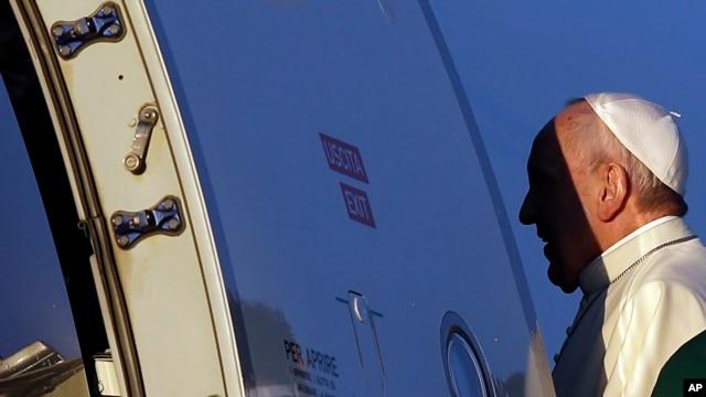 Paus Fransiskus naik ke pesawat untuk perjalanan ke Afrika, di bandar udara Roma (25/11). (AP/Gregorio Borgia)