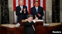 El presidente ucraniano, Petro Poroshenko, agradece la ovación recibida de parte de los legisladores estadounidenses. Aplauden atrás el vicepresidente Joe Biden y el presidente de la Cámara de Representantes, John Boehner.
