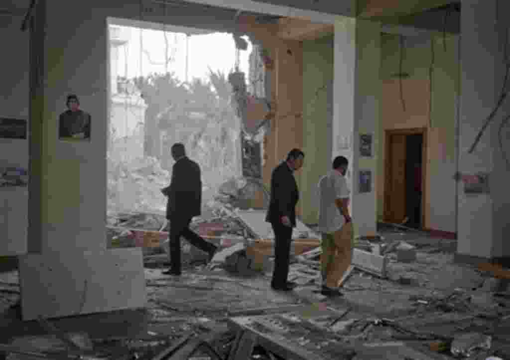 In this photo made on a government organized tour, officials inspect damage at the scene of an air strike, in Tripoli, Libya, Saturday, April 30, 2011. NATO bombed a government complex that included the state television building in Tripoli. The Libyans al