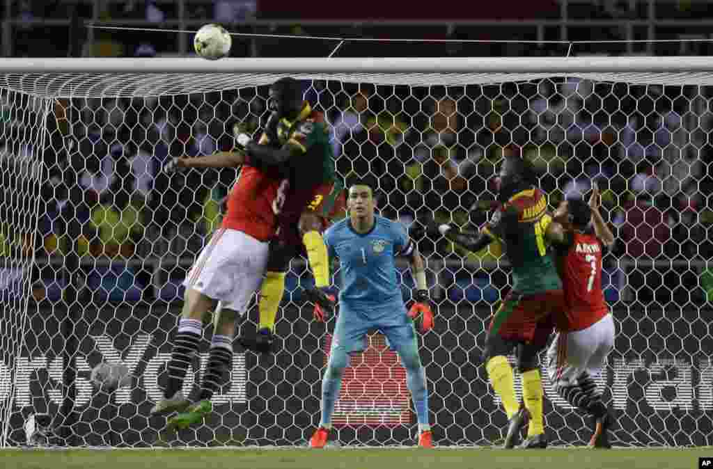 Egypt goalkeeper Essam El Hadary, center, watches as Cameroon's Nicolas Nkoulou, 2nd left, jumps to score his side's first goal during the African Cup of Nations final soccer match between Egypt and Cameroon at the Stade de l'Amitie, in Libreville, Gabon,