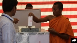 Cambodian Buddhist monk, right, casts his ballot in local elections at Wat Than pagoda's polling station in Phnom Penh, Cambodia, Sunday, June 3, 2012.
