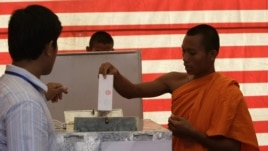 Cambodian Buddhist monk, right, casts his ballot in local elections at Wat Than pagoda's polling station in Phnom Penh, Cambodia, Sunday, June 3, 2012. Prime Minister Hun Sen's ruling party was expected to win the elections in a vote that monitors say is tainted by vote buying and other irregularities. (AP Photo/Heng Sinith)