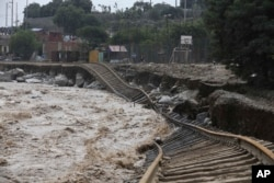 Train tracks lay destroyed in a flooded river in the Chosica district of Lima, Peru, Sunday, March 19, 2017. Intense rains and mudslides over the past three days have wrought havoc around the Andean nation.