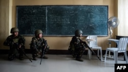 Philippine Army Scout Rangers crouch in a classroom during a mission to flush out Islamist militant snipers in Marawi, on the southern island of Mindanao, June 6, 2017.