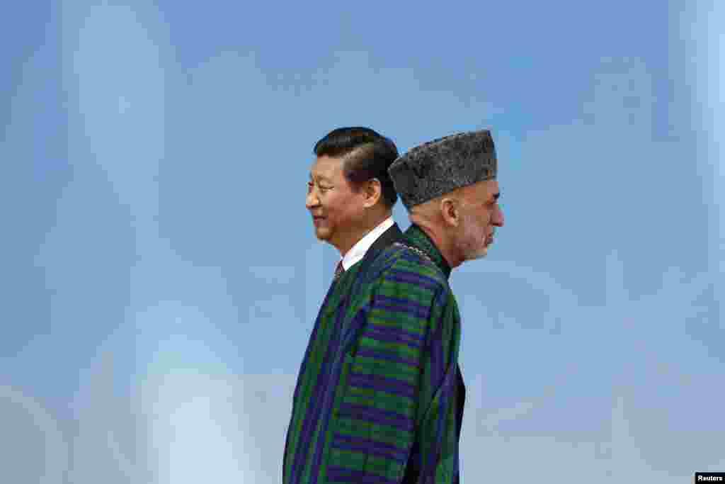 Tổng thống Afghanistan Hamid Karzai (phải) bước đi sau khi bắt tay với Chủ tịch Trung Quốc Tập Cận Bình trước lễ khai mạc tại Trung tâm Hội chợ Triển lãm trong Hội nghị lần thứ tư trong cuộc họp thưởng đỉnh về Tương tác và Các Biện pháp Xây dựng Lòng tin ở châu Á (CICA) ở Thượng Hải, Trung Quốc.