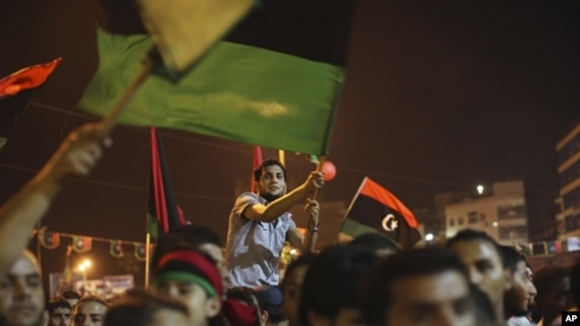 People celebrate the recent news of uprising in Tripoli against Moammar Gadhafi's regime at the rebel-held town of Benghazi, Libya, early Sunday, Aug. 21, 2011