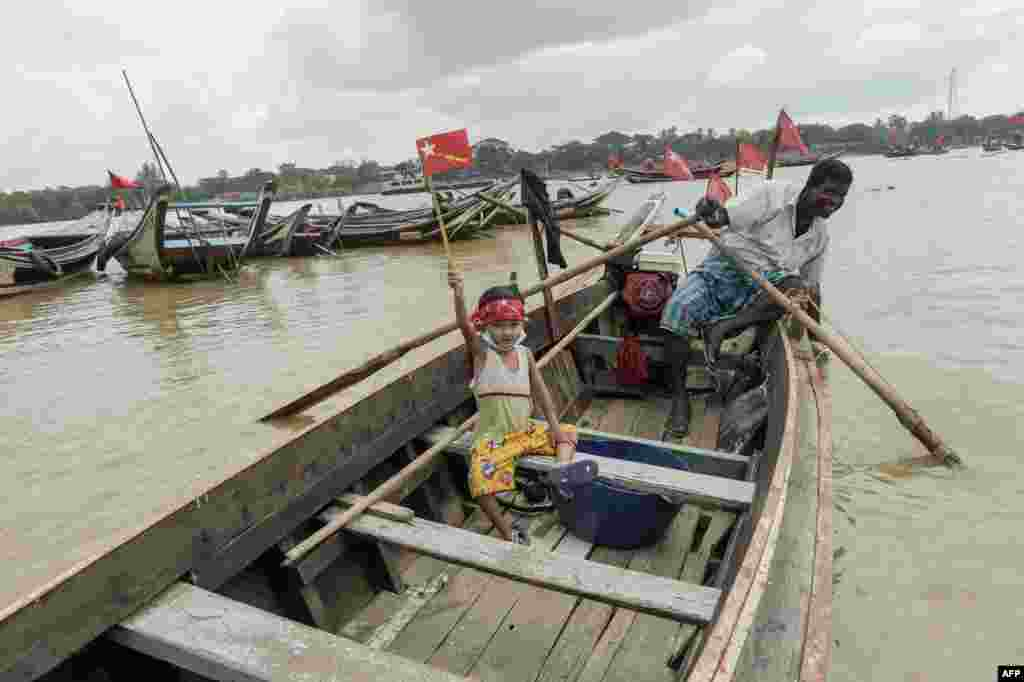 A child holds an emblem of the National League for Democracy as supporters ride on wooden boats in Yangon River, during an election campaign rally on the outskirts of Yangon, ahead of next month's elections.