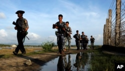 FILE - Myanmar police officers patrol along the fence bordering Bangladesh in Maungdaw, Rakhine State, Myanmar, Oct. 14, 2016.