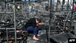 지난달 20일 그리스 북부 난민캠프에서 화재가 발생한 가운데 한 남성이 불에 탄 침대 위에서 머리를 숙이고 앉아있다. (자료사진)