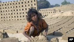 A 9-year-old girl toils under the hot sun, making bricks from morning to night, seven days a week.