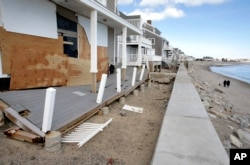 FILE - People walk along a beach near damaged beachfront homes, March 11, 2018, in Marshfield, Mass. The Northeast is bracing for its third nor'easter in fewer than two weeks.