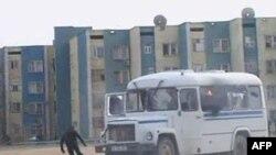 Một người biểu tình chạy tránh xe cảnh sát tại thị trấn Zhanaozen, Kazakhsatan, ngày 16 tháng 12, 2011