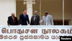 Britain's PM David Cameron (2nd L), Chief Minister of Northern province, C. V. Vigneswaran (2nd R) and Sri Lankan Tamil National Alliance (TNA) party leader R. Sampanthan (L) look out from the public library in Jaffna, north of Colombo, Nov. 15, 2013.