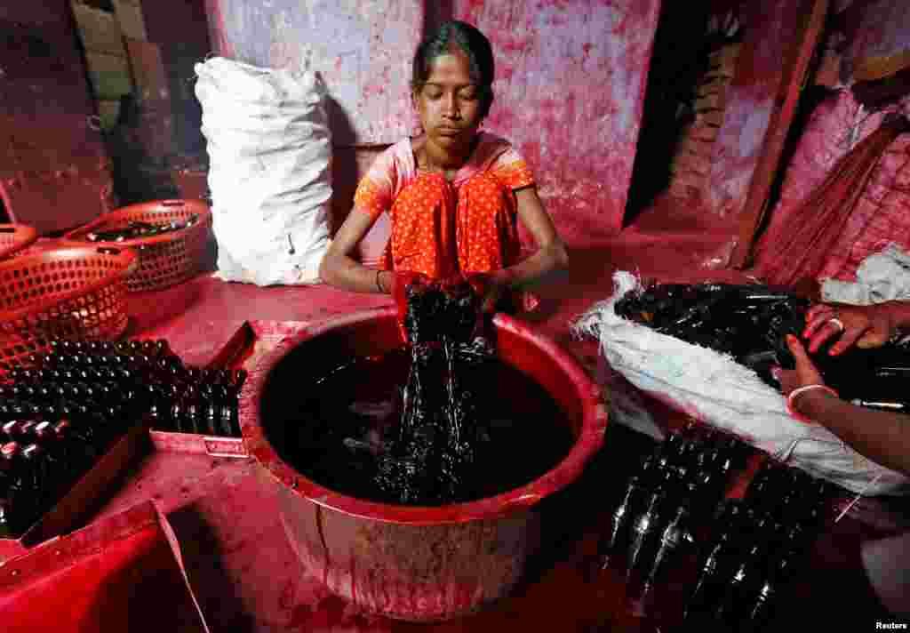 یک کارگر در شهر کلکتۀ هند در حال پر کردن بوتل ها با التا، مواد که زنان هندی برای آرایش دستها و پاها در مراسم عروسی و مذهبی استفاده می کنند.