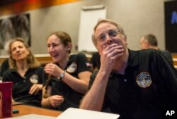"""2015年7月14日,""""新地平线""""科学团队成员收到探测器在驶向距离冥王星最近位置之前发来的最后也是最清晰的照片后欢欣鼓舞。(NASA图片)"""